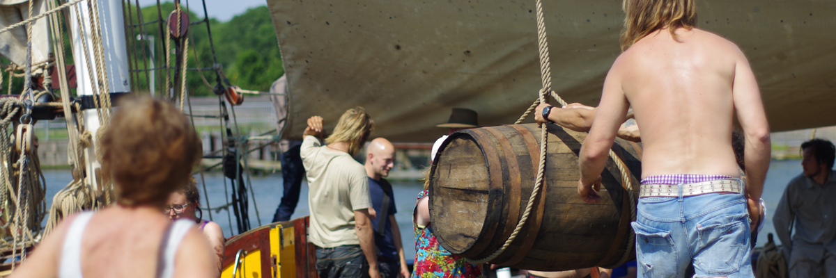 Unloading rum and cocoa from the sailing ship 'Tres Hombres' in Amsterdam Noord